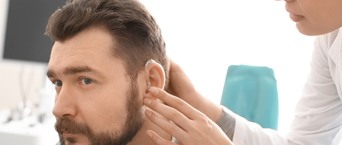 A Doctor or Audiologist Wearing Hearing Aid To Her Patient.