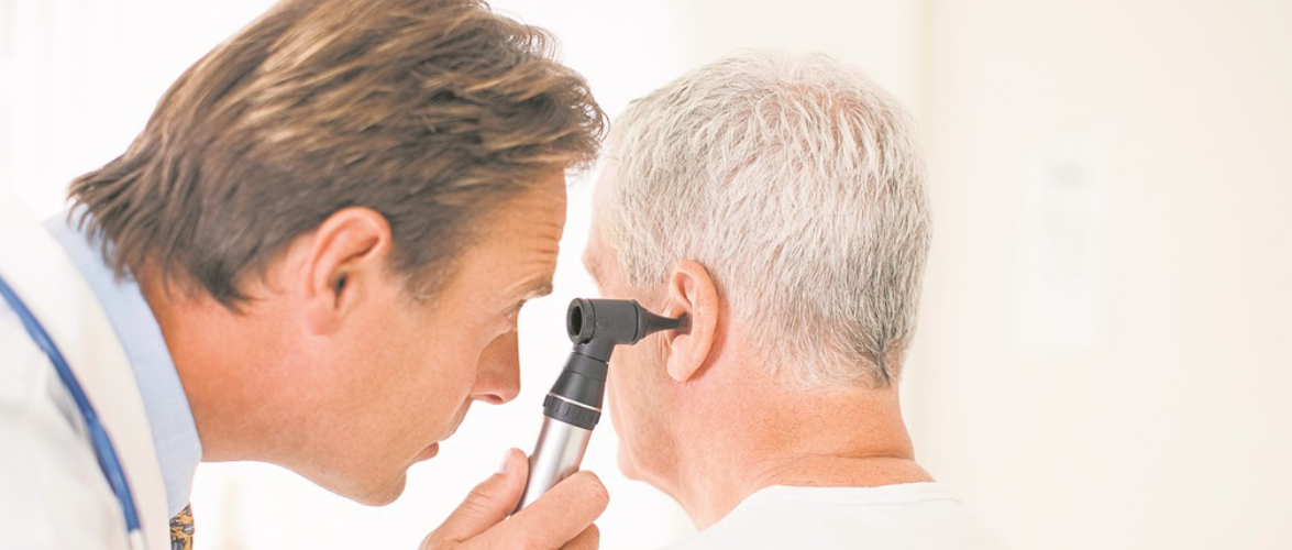 An Audiologist Examining An Old Man Ear With Otoscope.