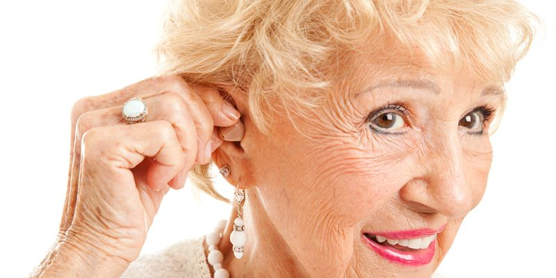 Closeup of A Senior Woman Inserting Hearing Aid In Her Ear.