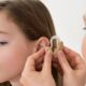 A Doctor Putting Hearing Aid In The Ear of A Girl.